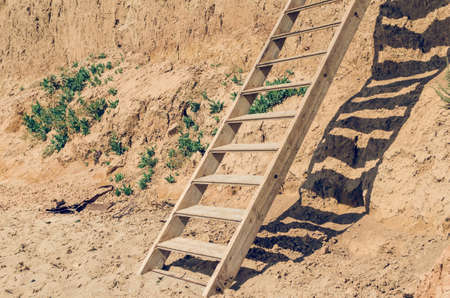 Wooden staircase attached to a clay rock on a sunny day. Banco de Imagens
