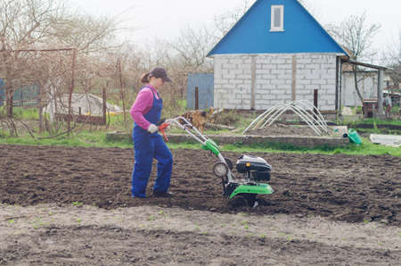 Young girl working in a spring garden with a cultivator.