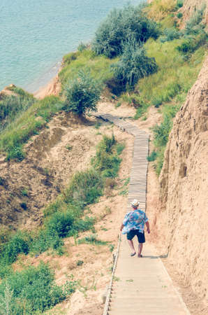 Young man in a hat goes down the stairs to the sea.