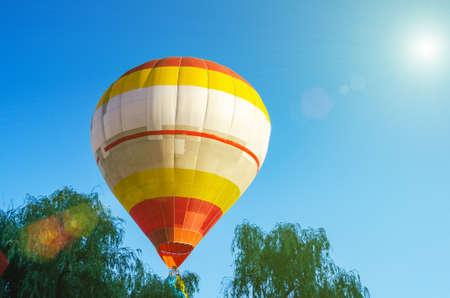 Une montgolfière colorée vole dans le ciel bleu au-dessus des arbres.