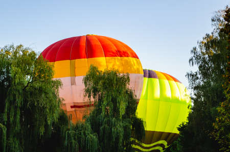 Colorful hot air balloon is flying in the blue sky above the trees.