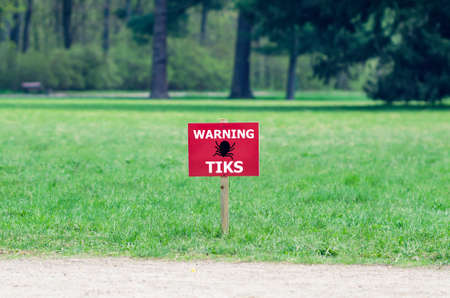 The sign on the lawn with the inscription: warning ticks. Stock Photo