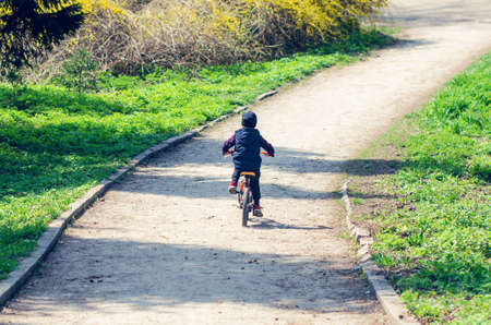 Little boy riding a bike in the spring city park.