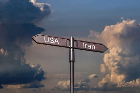Road sign with the inscription USA, Iran on the background of a stormy sky.