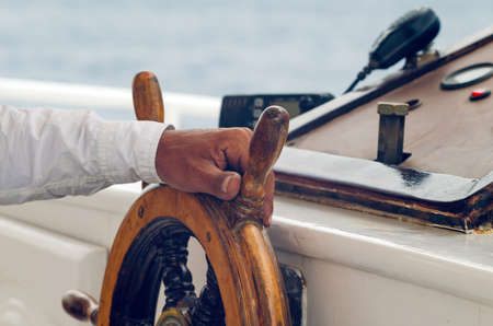 Hands of the captain holding the wheel on the deck of the ship.
