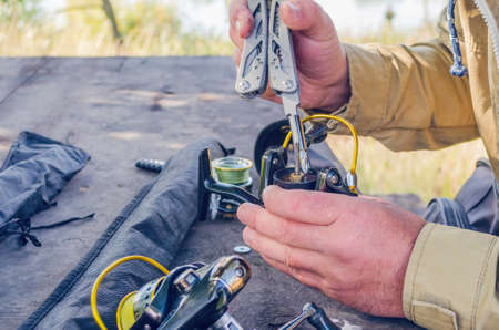 a man repairs a fishing reel with improvised means.