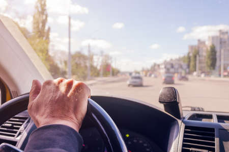 The driver's hands on the steering wheel of the car. Stock Photo