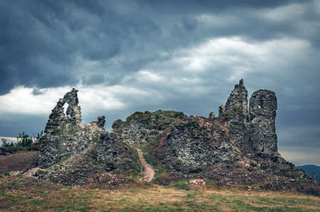 The ruins of an old castle in Khust, Transcarpathia Ukraine, against a background of thunderclouds. Stok Fotoğraf
