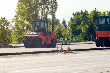 Road works, compaction of the pavement using an asphalt roller.