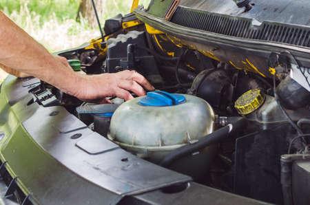 The mechanics hands performing a car engine check.