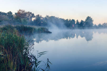 Morning landscape with fog over the lake.
