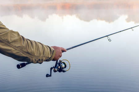 Hands of a fisherman with a spinning rod and coil summer morning on the lake.