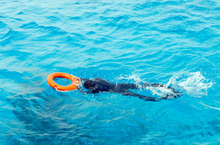 A young man in a diving suit and flippers swims in the sea holding the lifebuoy. Stok Fotoğraf