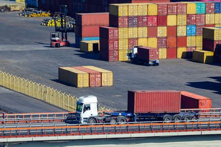 A truck transports a container in a storage area of a cargo sea port. Stok Fotoğraf