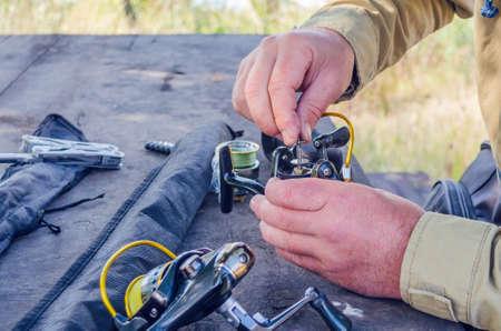 un homme répare un moulinet de pêche avec des moyens improvisés.