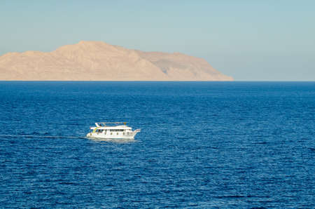 Pleasure tourist boat with passengers sailing in the clear blue water of the Red Sea Stok Fotoğraf