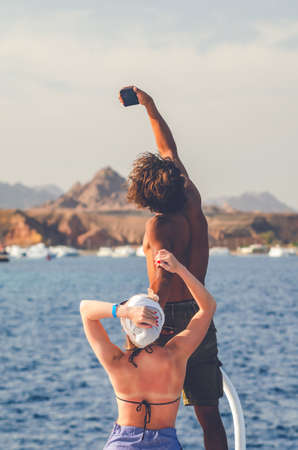 Dark curly guy with a white girl take a selfie on a smartphone on the background of the sea and mountains, view from the back