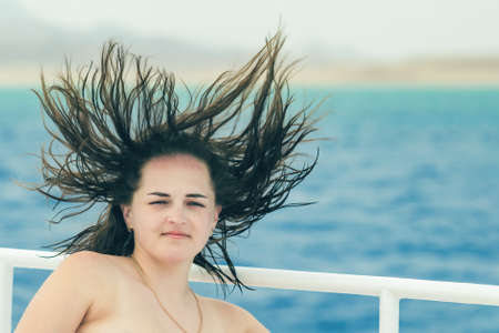 Portrait of a beautiful girl with freckles, the wind develops hair on a background of blue sea. Stok Fotoğraf