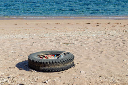 An old car tire and plastic waste are lying on the sandy seashore. Stok Fotoğraf