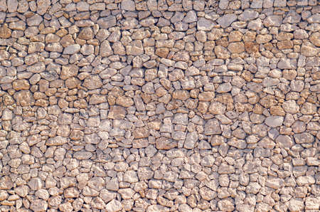 Old beige stone wall background texture close up.