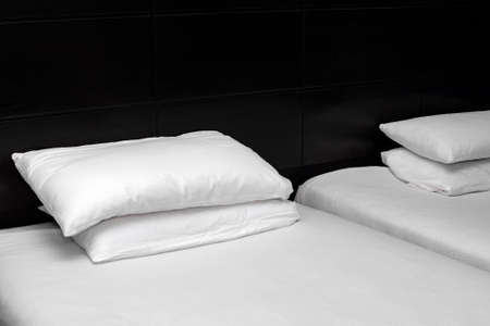 White sheets and pillow at the head of the black bed. Stok Fotoğraf