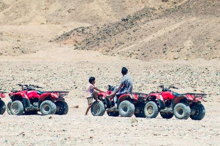 Dahab, Egypt May 11, 2019: Egyptian boys sit on ATVs in the desert.