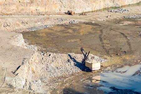 Excavatrice dans une carrière de pierre pour l'extraction de pierre concassée et de gravier pour une utilisation dans la construction.