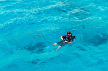 Sharm El Sheikh, Egitto, 8 maggio 2019: Un uomo in attrezzatura subacquea nuota nelle limpide acque blu del mare.