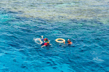 Sharm El Sheikh, Egypt, May 8, 2019: People in snorkeling gear swimming in the clear blue water of the sea. Reklamní fotografie