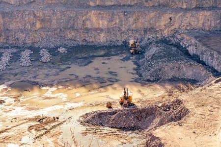 Excavator and heavy mining truck in a granite quarry. 版權商用圖片