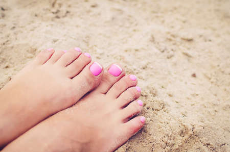 Female legs in the sand with a french pedicure.