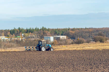 The tractor plows a field, cultivates the soil for sowing grain.