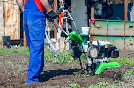 A man plows the land with a cultivator in a spring garden.