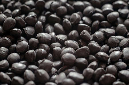 Black polymer dye in granules, background texture.