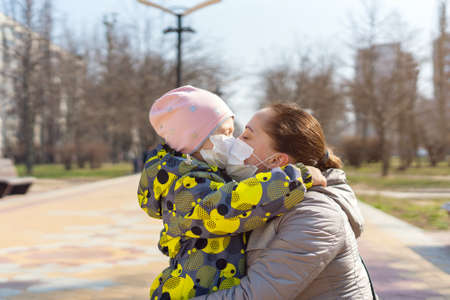 Young mother kisses her daughter through protective medical masks. Covid-19 Coronavirus Pandemic, Virus Protection.