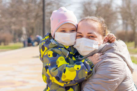 Young mother with daughter in protective masks. Covid-19 Coronavirus Pandemic, Virus Protection.