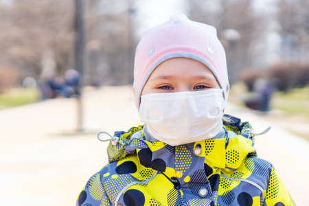 Portrait of a little girl in a medical protective mask on her face, Covid-19 coronavirus pandemic, virus protection.