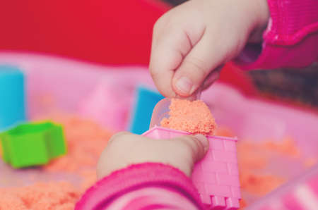 The hands of a child playing with kinetic sand. Zdjęcie Seryjne