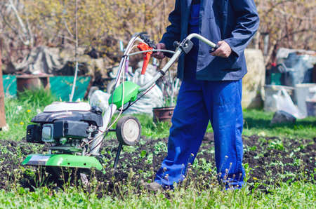 A man cultivates the land with a cultivator in a spring garden. Zdjęcie Seryjne