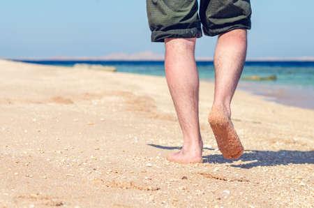Barefoot man walks along the sandy sea coast. Banque d'images