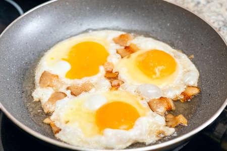 Fried eggs with bacon in a pan. Zdjęcie Seryjne