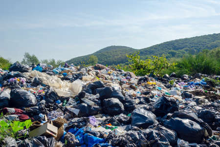 Garbage dump on a background of mountains, environmental pollution.