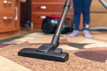 A small child vacuums a carpet with a vacuum cleaner. Stockfoto
