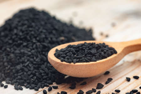 Black cumin seeds on wooden spoon on wooden background.