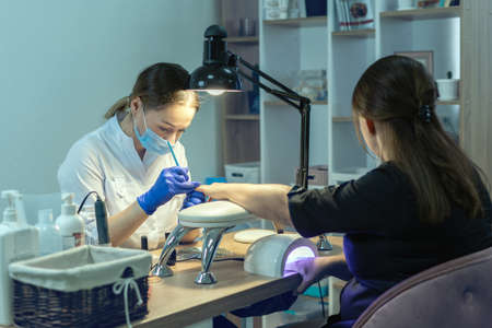 Manicurist doing a manicure in a nail salon, applying varnish on nails.