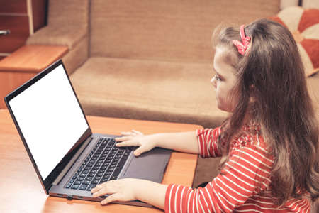 Little girl using laptop for distance learning or for fun.