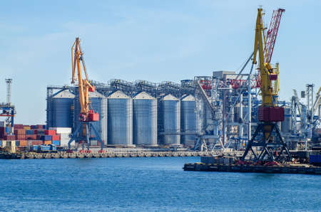 Lifting harbor cranes, shipping containers and granaries in the cargo seaport. Stock Photo
