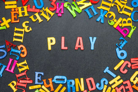 Play, word made from bright color letters on black background.