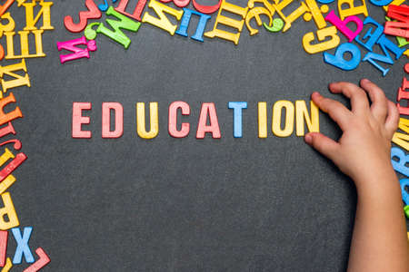 Child's hand laid out the word education from multicolored plastic letters.