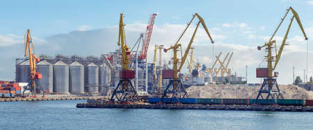 Port panorama, harbor cranes and granaries in the cargo seaport.